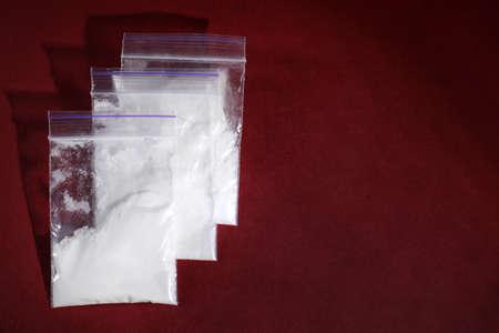 Cocaína en bolsas de plástico sobre fondo de color, vista superior. Espacio para texto