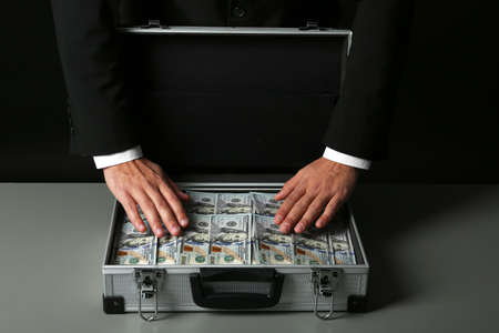 Businessman with suitcase full of money on dark background