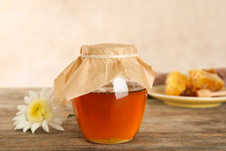Jar with sweet honey on table against color background