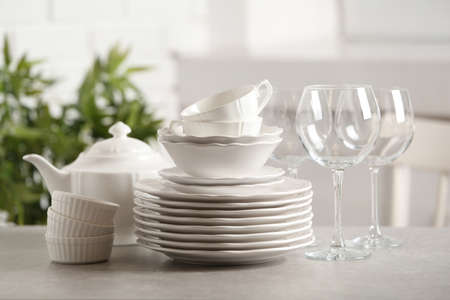 Set of clean dishes on table against blurred background Imagens