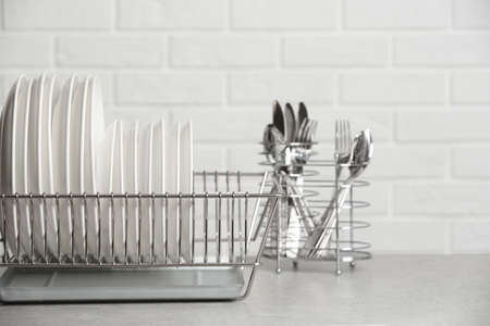 Dish rack with clean plates on table near brick wall. Space for text