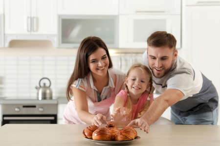 Happy family with freshly oven baked buns at table in kitchen Zdjęcie Seryjne