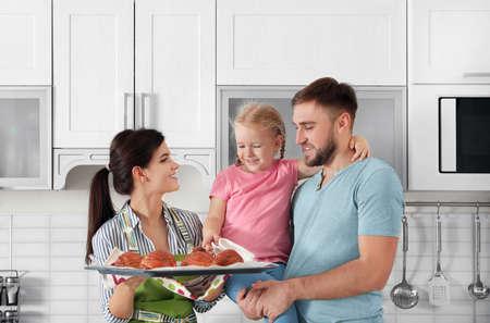 Piękna kobieta częstująca swoją rodzinę świeżo upieczonymi bułeczkami w kuchni