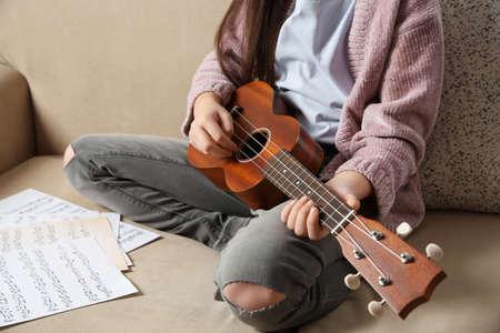 Little girl playing guitar on sofa, closeup