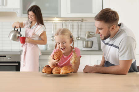 Happy couple treating their daughter with freshly oven baked bun in kitchen