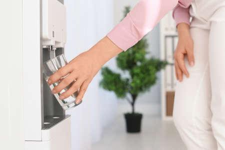 Mujer llenando el vaso del enfriador de agua en el lugar de trabajo, primer plano