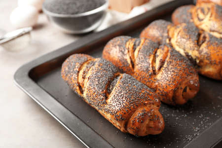 Baking tray with tasty poppy seed rolls  on table