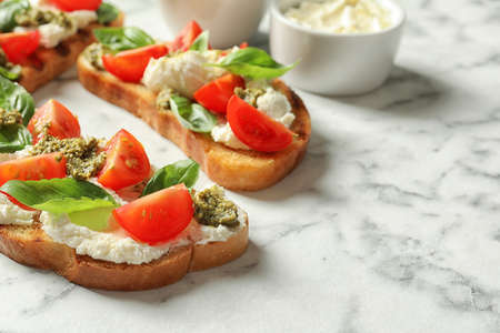 Toasted bread with tasty cream cheese and tomatoes on marble table. Space for text