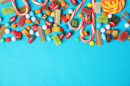 Flat lay composition with different yummy candies and space for text on color background Stock Photo