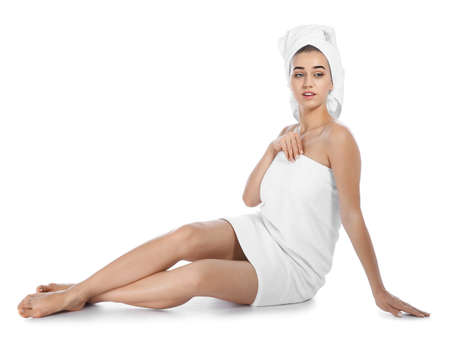 Portrait of young pretty woman with towels sitting on white background