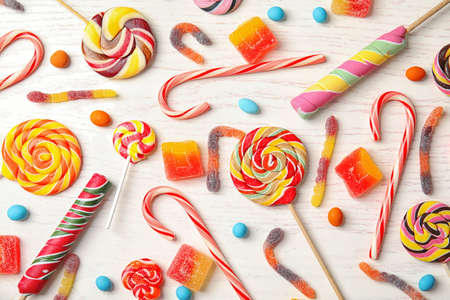 Many different yummy candies on white wooden background, top view