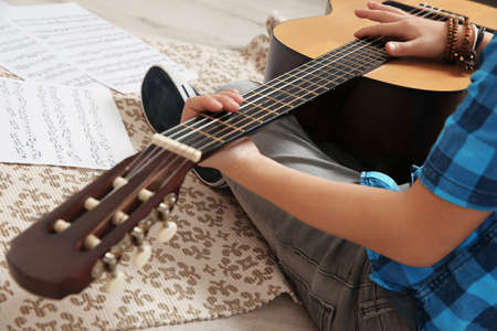 Little boy playing guitar on floor, closeup 写真素材