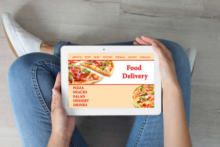 Woman using tablet to order food delivery at home, top view Foto de archivo