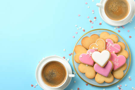 Romantic breakfast with heart shaped cookies and cups of coffee on color background, flat lay. Space for text Stock Photo