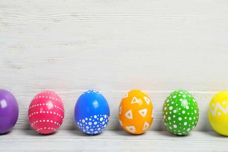 Decorated Easter eggs on table near wooden wall. Space for text