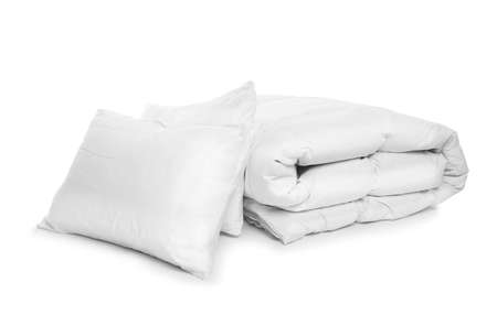 Clean blanket and pillows on white background Фото со стока