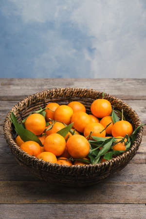 Fresh ripe tangerines in wicker basket on wooden table. Space for text