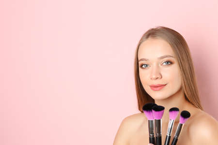 Portrait of beautiful young woman with makeup brushes on color background. Space for text