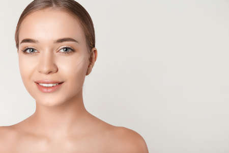 Portrait of beautiful young woman with makeup smears on face against white background