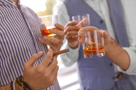Grupa przyjaciół pijących razem whisky w pomieszczeniu, zbliżenie