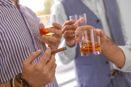 Grupo de amigos bebiendo whisky juntos en el interior, primer plano