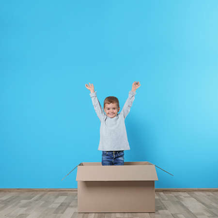 Cute little boy playing with cardboard box near color wall Stock Photo