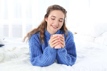 Beautiful teenage girl in warm cozy sweater with cup of hot drink on bed at home Stock Photo