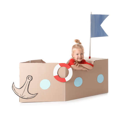 Cute little girl playing with cardboard ship on white background