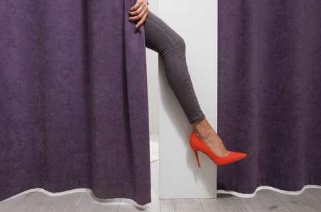 Femme derrière le rideau du dressing montrant la jambe dans un magasin de mode