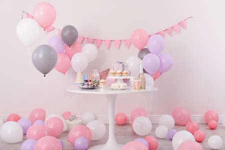 Party treats and items on table in room decorated with balloons Foto de archivo