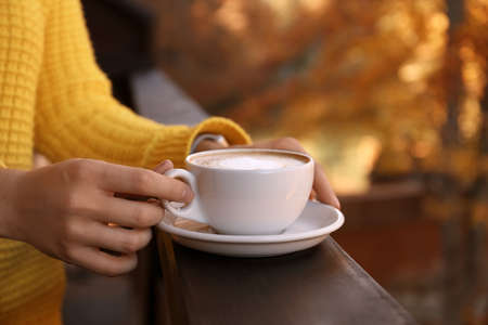 Woman in warm sweater holding cup with hot cozy drink on wooden railing at balcony