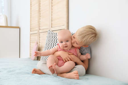 Cute boy kissing his little sister on bed at home Imagens