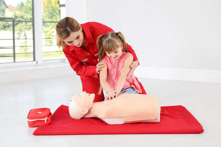 Instructor with little girl practicing first aid on mannequin indoors