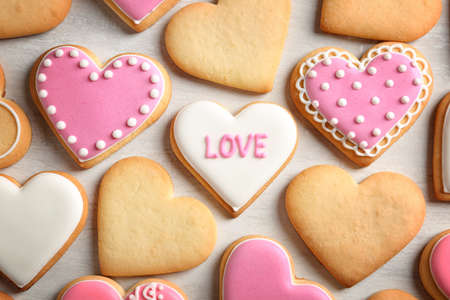 Decorated heart shaped cookies on color background, top view. Valentine's day treat