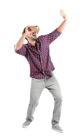 Young man using cardboard virtual reality headset, isolated on white