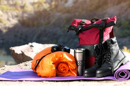 Set of camping equipment with sleeping bag on ground outdoors