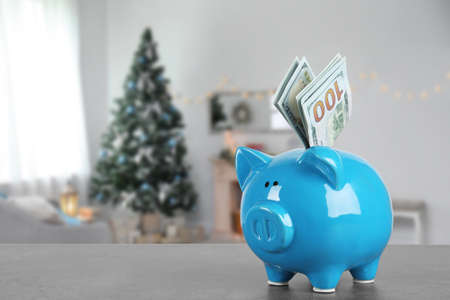 Piggy bank with money on table in living room decorated for Christmas. Space for text