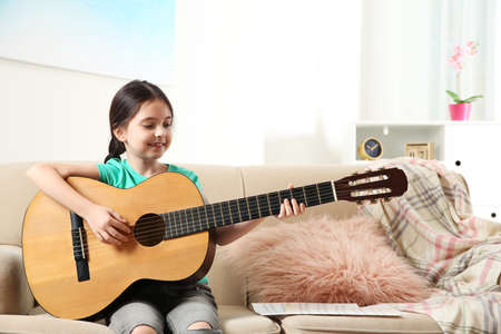 Cute little girl playing guitar on sofa in room. Space for text