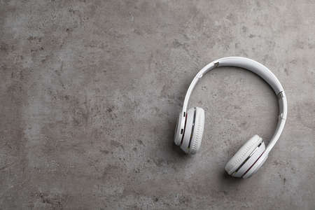 Stylish modern headphones and space for text on gray background, top view