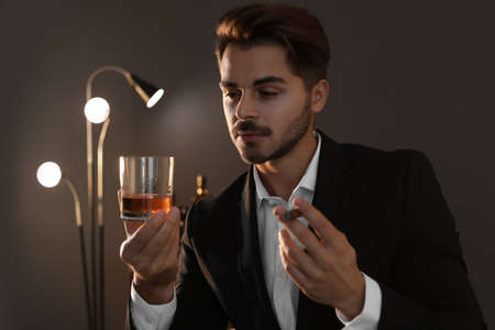 Young man with glass of whiskey and cigar at home