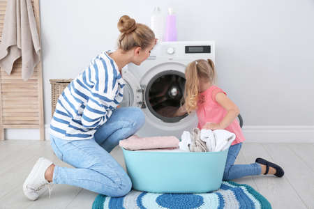 Little girl helping her mother to do laundry at home