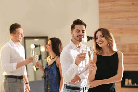 Friends clinking glasses with champagne at party indoors Standard-Bild