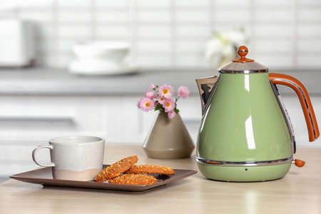 Stylish electrical kettle, cup and cookies on table against blurred room interior. Space for text