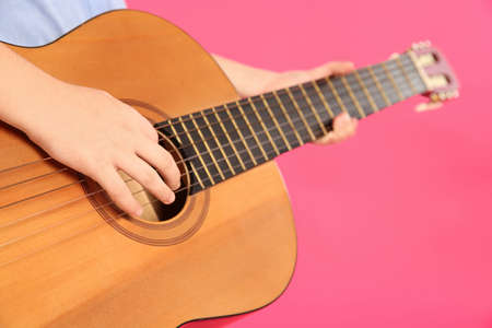 Little girl playing wooden guitar on color background, closeup