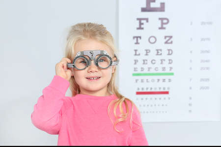 Little girl with trial frame near eye chart in hospital, space for text. Visiting children's doctor Zdjęcie Seryjne