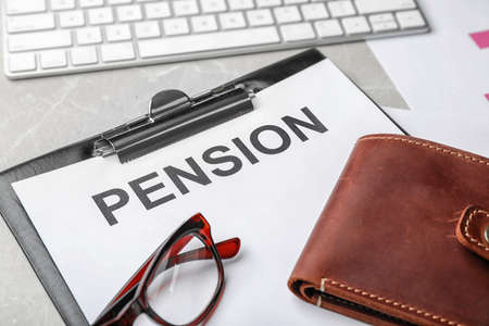 Glasses, wallet and paper with word PENSION on table Stock Photo
