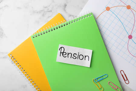 Paper with word Pension, notebooks and chart on table, top view