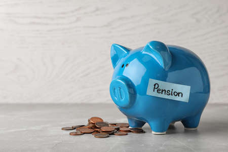Piggy bank with word PENSION and coins on table. Space for text Stock Photo
