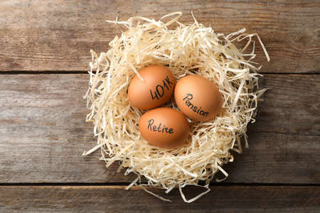 Eggs with words PENSION, RETIRE and 401k in nest on wooden background, top view