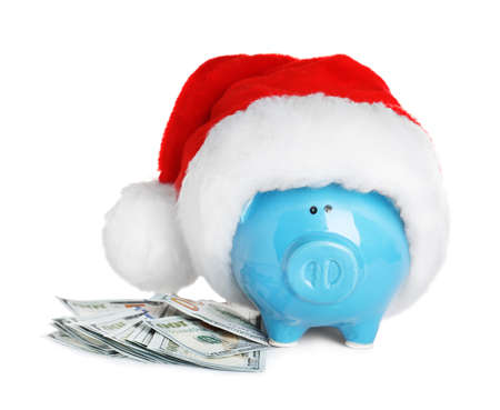 Piggy bank with Santa hat and dollar banknotes on white background
